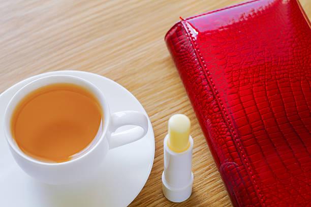 . tasse tee, lippenstift und geldbeutel. - natürliche make up kurse stock-fotos und bilder