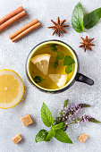 Cup of tea, mint and lemon, brown sugar cinnamon and anise on a grey table