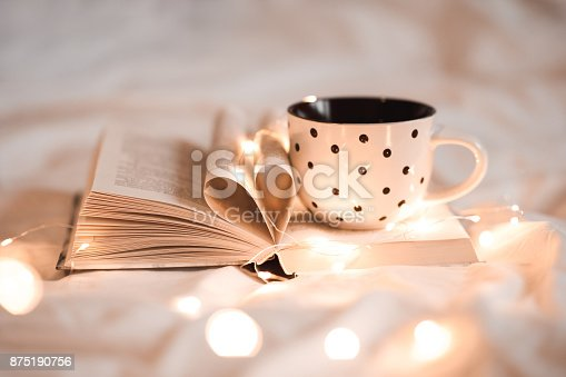 istock Cup of tea on open book 875190756