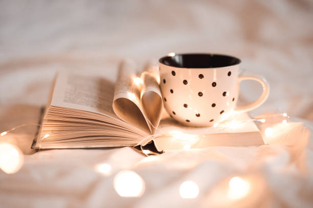 Cup of tea on open book stock photo