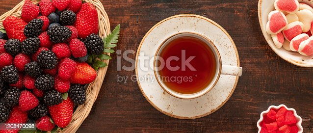 863562090 istock photo A cup of tea on the table with berries and sweets. Banner. Berry tea on a wooden background. Food tea concept. Top view. 1208470098