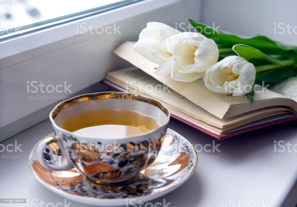 Cup of tea on the windowsill, open book, 3 white tulips, flowers