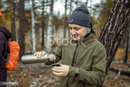 A hikers are stopping to rest in the forest. The man is standing , pours a cup of tea from a thermos. Shooting at cloudy autumn day