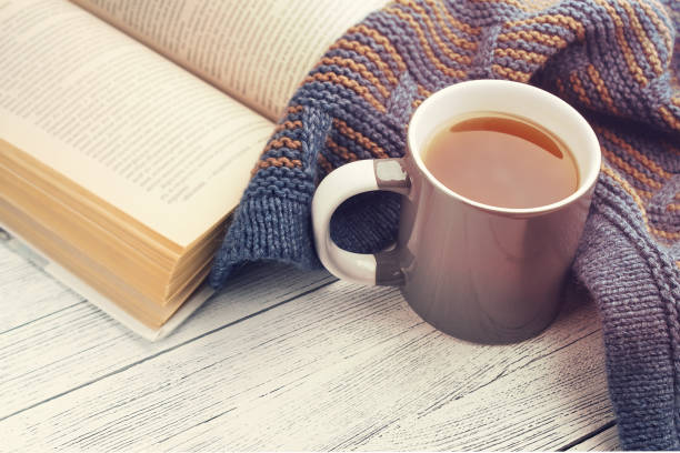 Xícara de chá, livro aberto e fêz malha o lenço na luz de fundo de madeira - foto de acervo