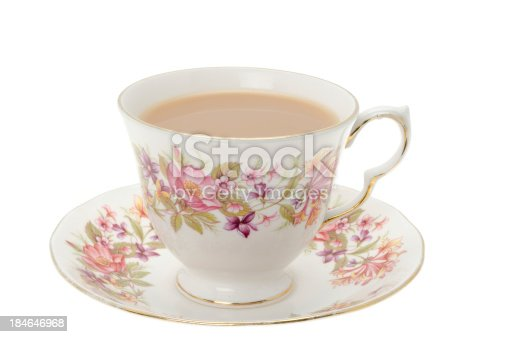 A cup of hot tea served in an ornate patterned cup and saucer - studio shot.