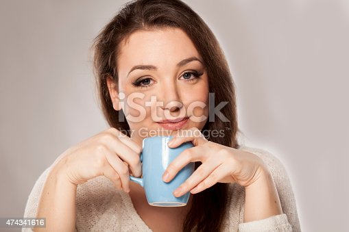 positive young woman holding a cup of tea on grey background