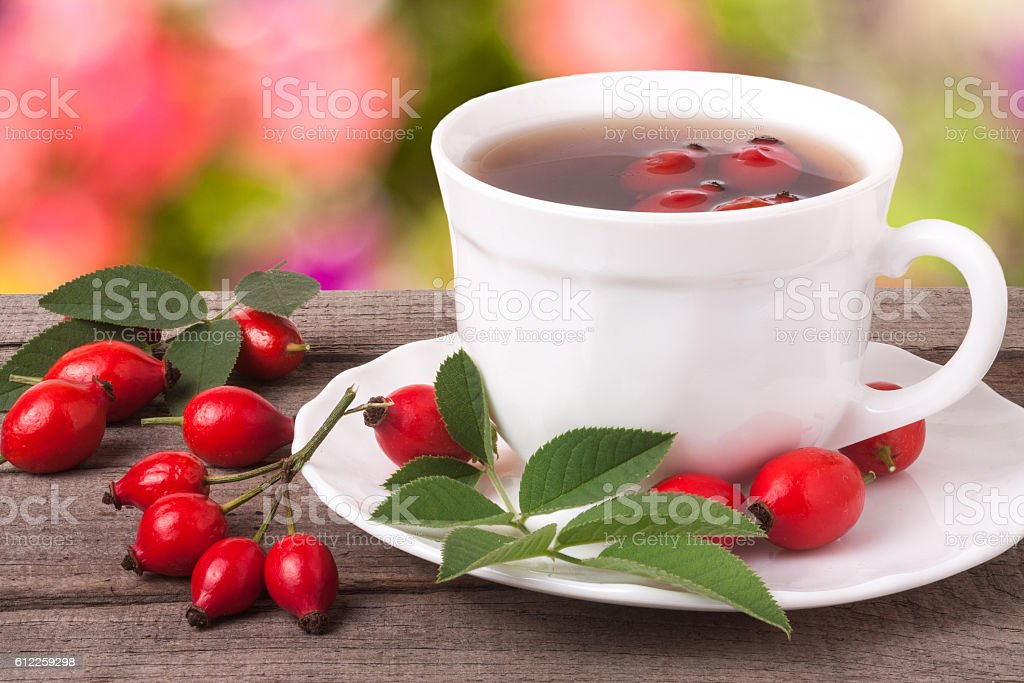 cup of tea rosehip berries on a dark wooden background stock photo