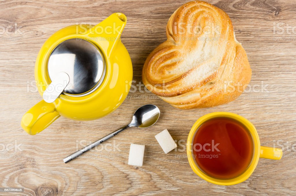 Cup of tea, teapot and bun with sugar on table royalty free stockfoto