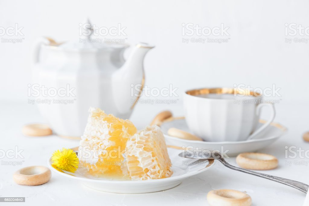 Cup of tea, teapot and honeycomb on a plate, withhoneycomb on background 免版稅 stock photo