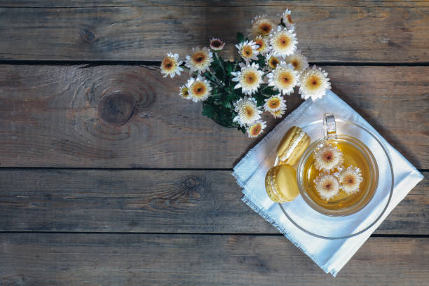 Cup of tea with chrysanthemum flowers and macaroons stock photo