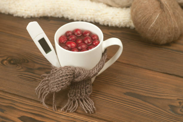 Cup of tea with cranberries, scarf, thermometer - the concept of seasonal respiratory diseases, treatment of colds Cup of tea with cranberries, scarf, thermometer - the concept of seasonal respiratory diseases, treatment of colds antipyretic stock pictures, royalty-free photos & images