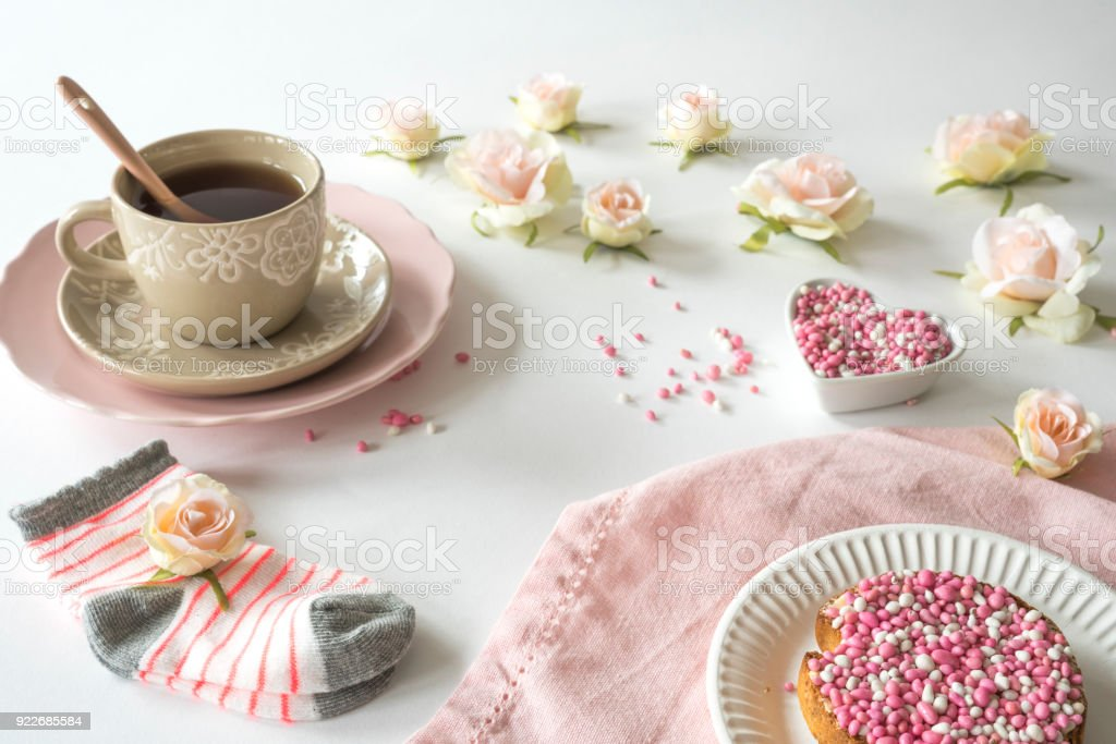 cup of tea with crispy rusk with traditional Dutch food pink muisjes, aniseed, baby socks, roses for celebration birth of a daughter stock photo