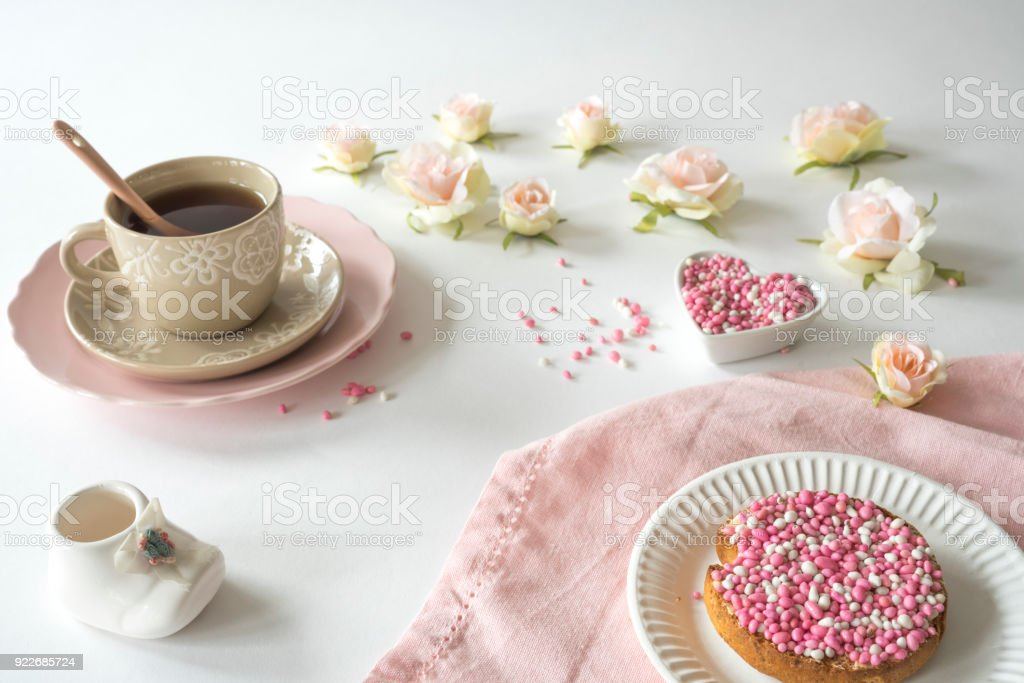 cup of tea with crispy rusk with traditional Dutch food pink muisjes, roses, cute baby shoe, aniseed, for celebration birth of a daughter stock photo