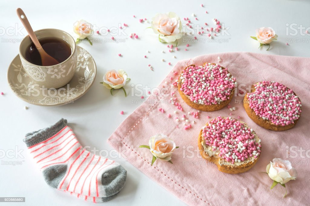 cup of tea with crispy rusk with traditional Dutch food pink muisjes, aniseed, cute baby socks, roses, for celebration birth of a daughter stock photo