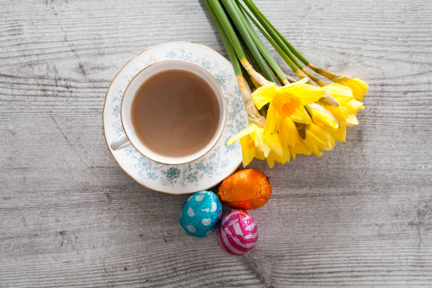 Cup of tea with Daffodils and chocolate Easter eggs stock photo