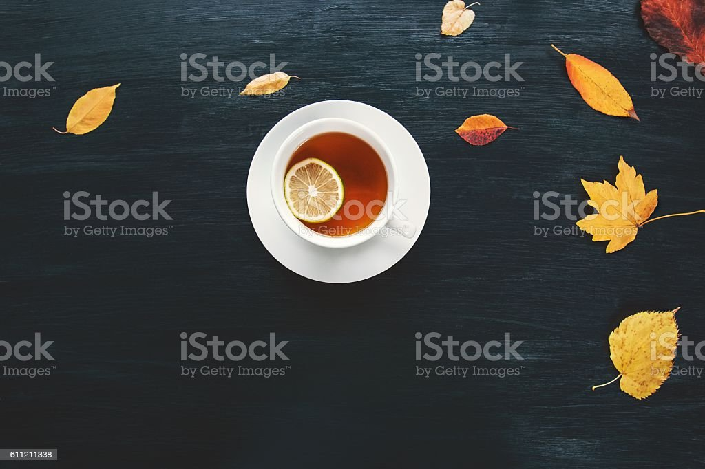 Cup of Tea with fall yellow leaves on wooden background stock photo