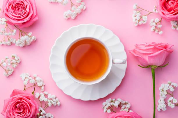 tasse tee mit frischen blumen auf rosa hintergrund. ansicht von oben. textfreiraum - rosen tee stock-fotos und bilder