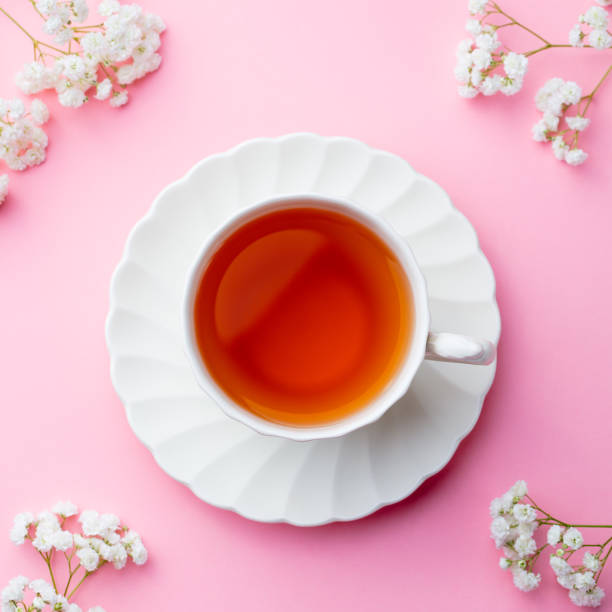 Cup of tea with fresh flowers on pink background. Top view. Copy space. - foto stock