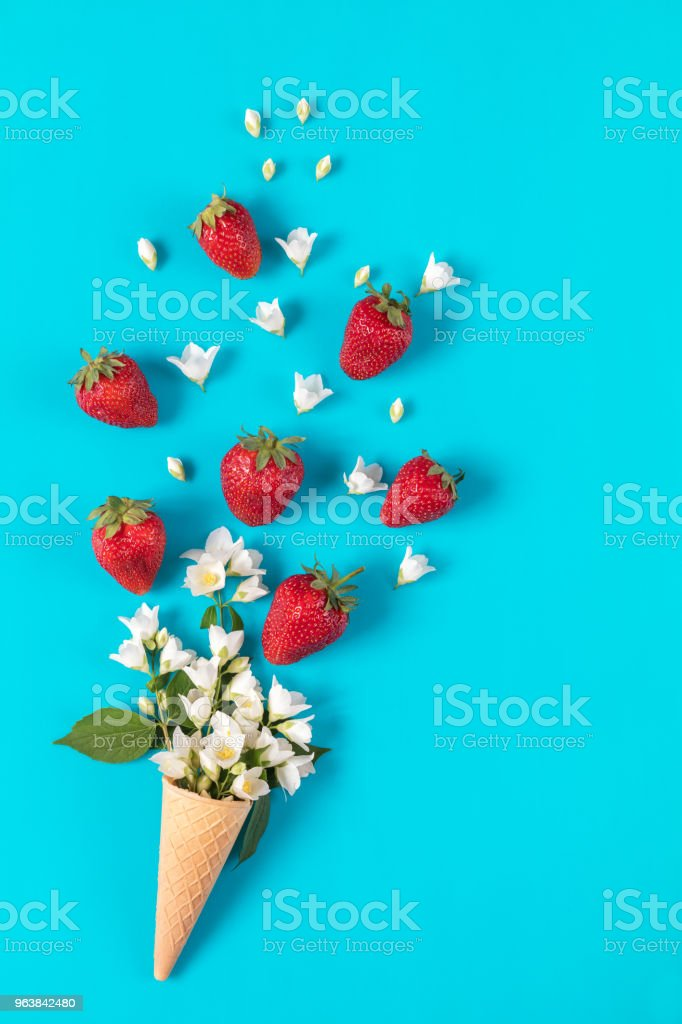 Cup of tea with fresh strawberries and flowers jasmine blossom bouquets on blue surface. royalty-free stock photo