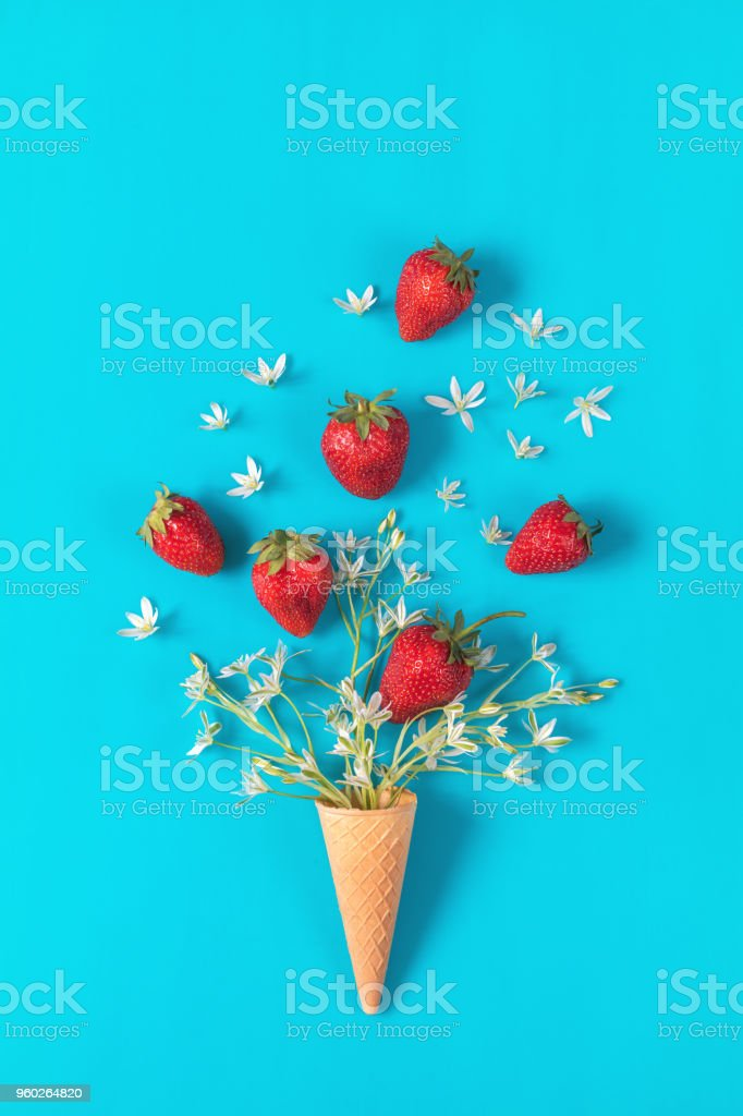 Cup of tea with fresh strawberries and flowers ornithogalum blossom  bouquets on blue surface. stock photo