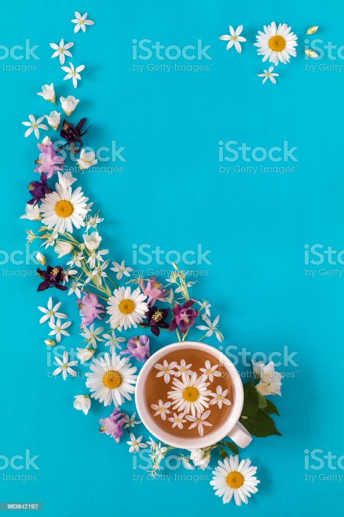 Cup of tea with fresh strawberries, marshmallows and flowers blossom bouquets on blue surface - Royalty-free Above Stock Photo