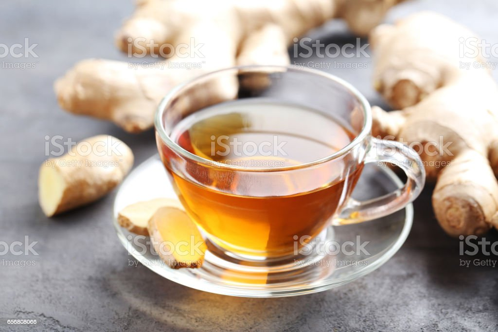 Cup of tea with ginger root on grey wooden table stock photo