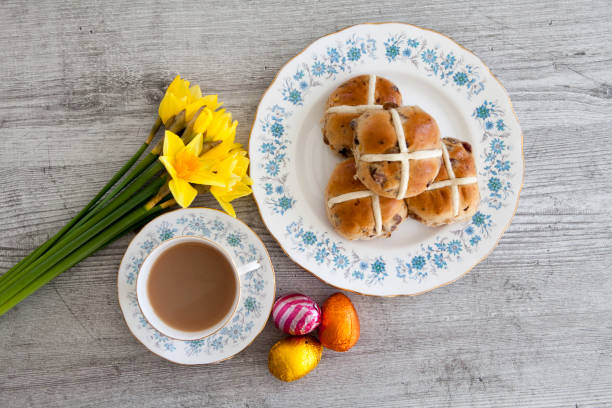 Cup of tea with hot cross buns, chocolate eggs and daffodils stock photo