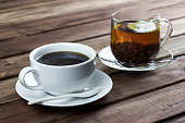 cup of tea with lemon and a cup of coffee on a wooden surface, the choice between coffee and tea