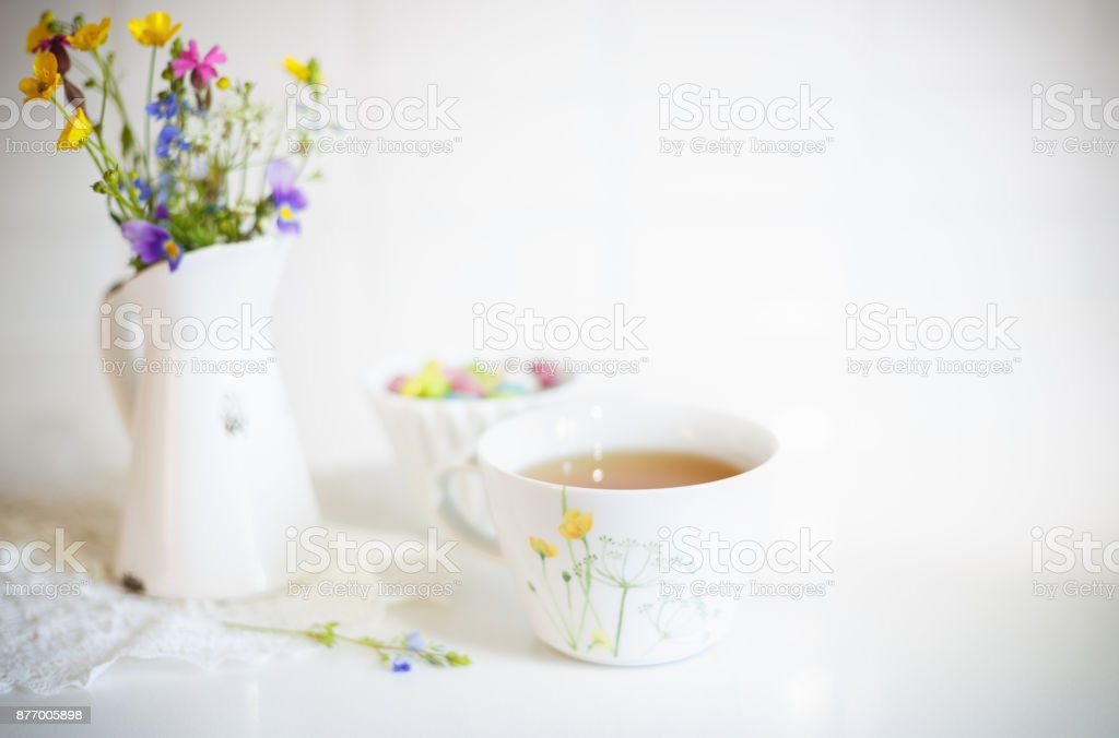 Cup of tea with meadow's flowers in vase stock photo