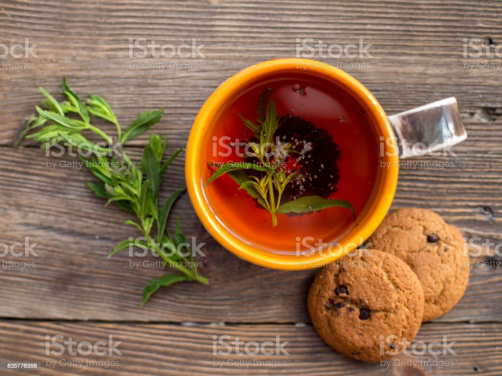 Cup of tea with mint and cakes stock photo