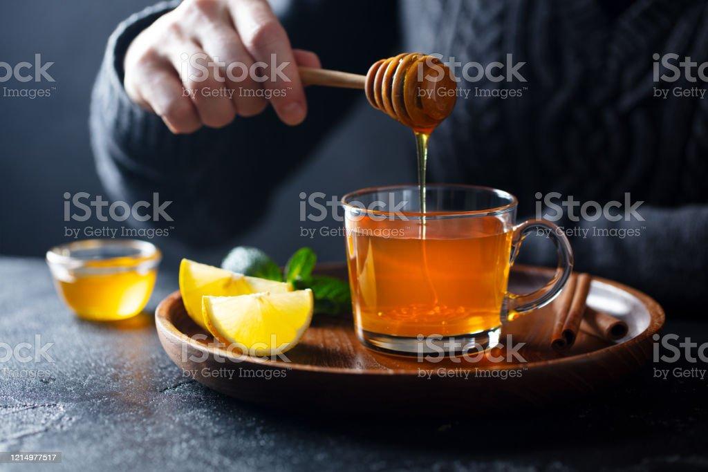 Tazza di tè con versando miele e limone. Sfondo grigio. - Foto stock royalty-free di Accogliente