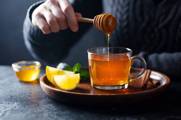 Cup of tea with pouring honey and lemon. Grey background. stock photo