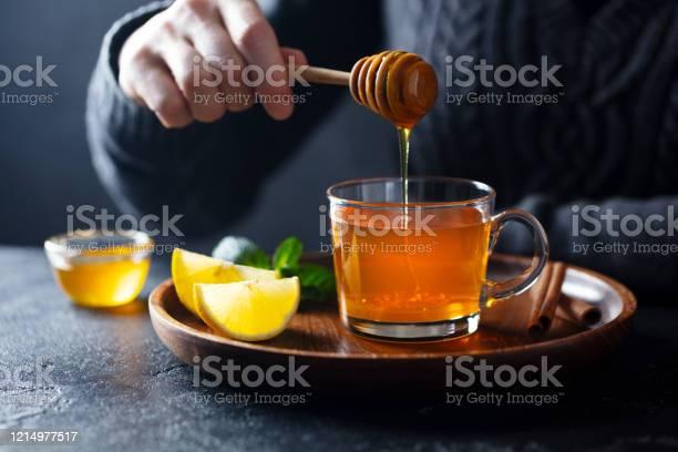 Tazza Di Tè Con Versando Miele E Limone Sfondo Grigio - Fotografie stock e altre immagini di Accogliente