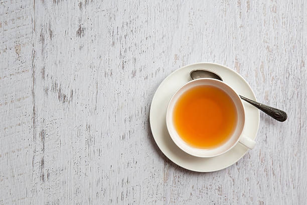 Cup of tea with spoon on white background stock photo