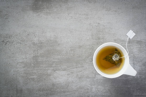 Cup of tea with teabag Cup of tea with teabag, on concrete stone background tea crop stock pictures, royalty-free photos & images