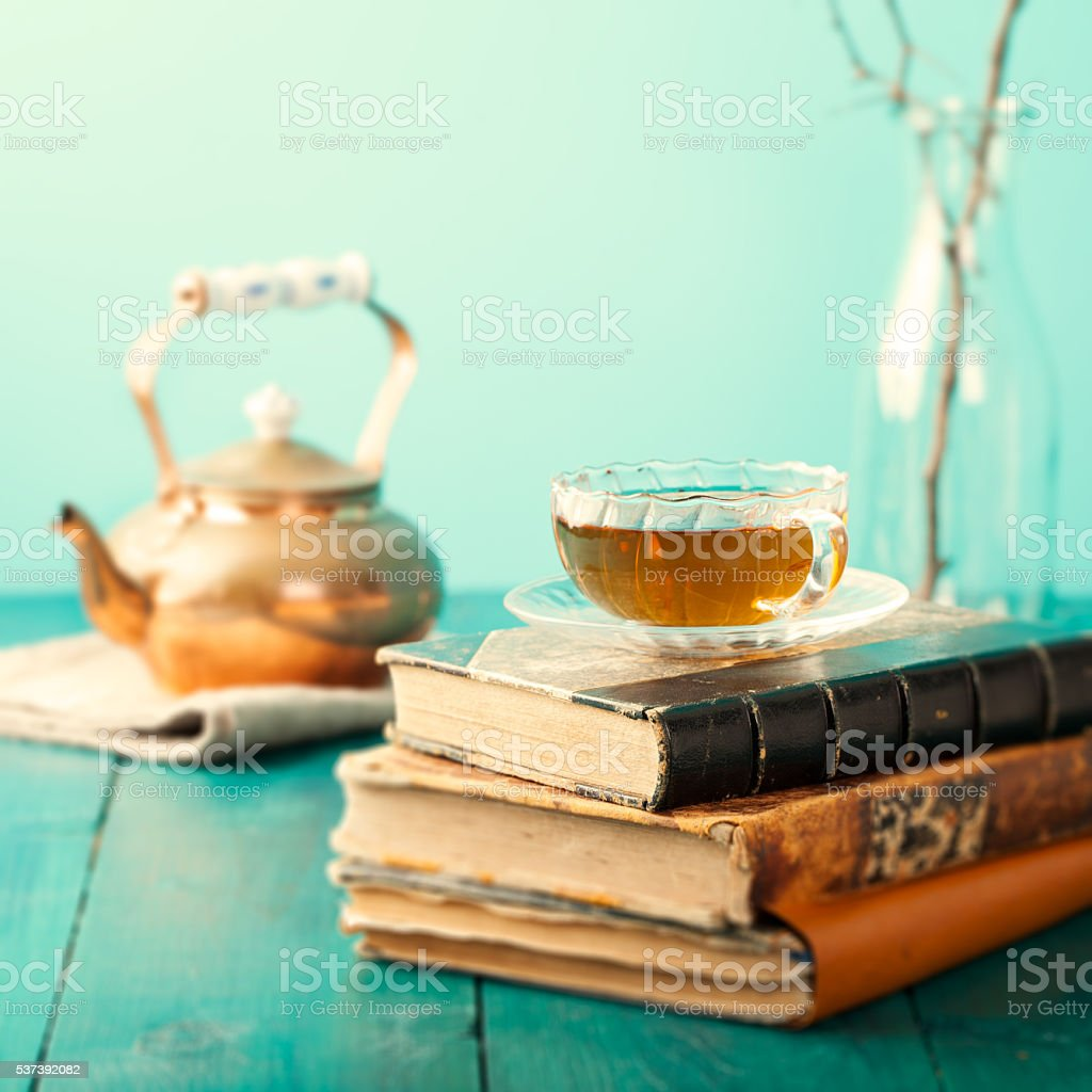 Cup of tea with teapot, vintage books on wooden table stock photo