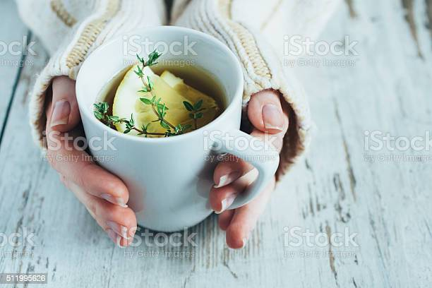 Human hands holding cup of tea with thyme herb and lemon slices on a wooden table,.