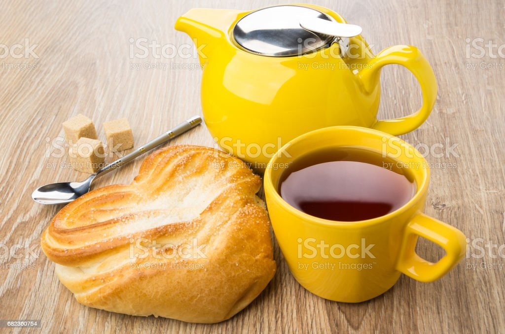Cup of tea, yellow teapot, spoon and bun with sugar foto stock royalty-free