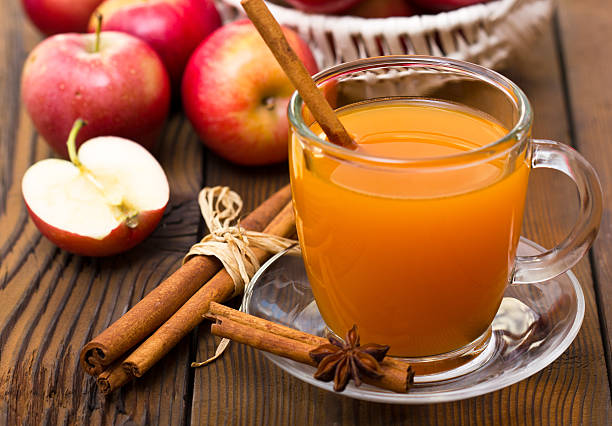 A cup of warm apple cider with cinnamon Hot apple cider with cinnamon stick hot apple cider stock pictures, royalty-free photos & images