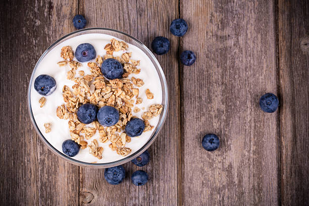 Cup of yogurt with granola and blueberries stock photo