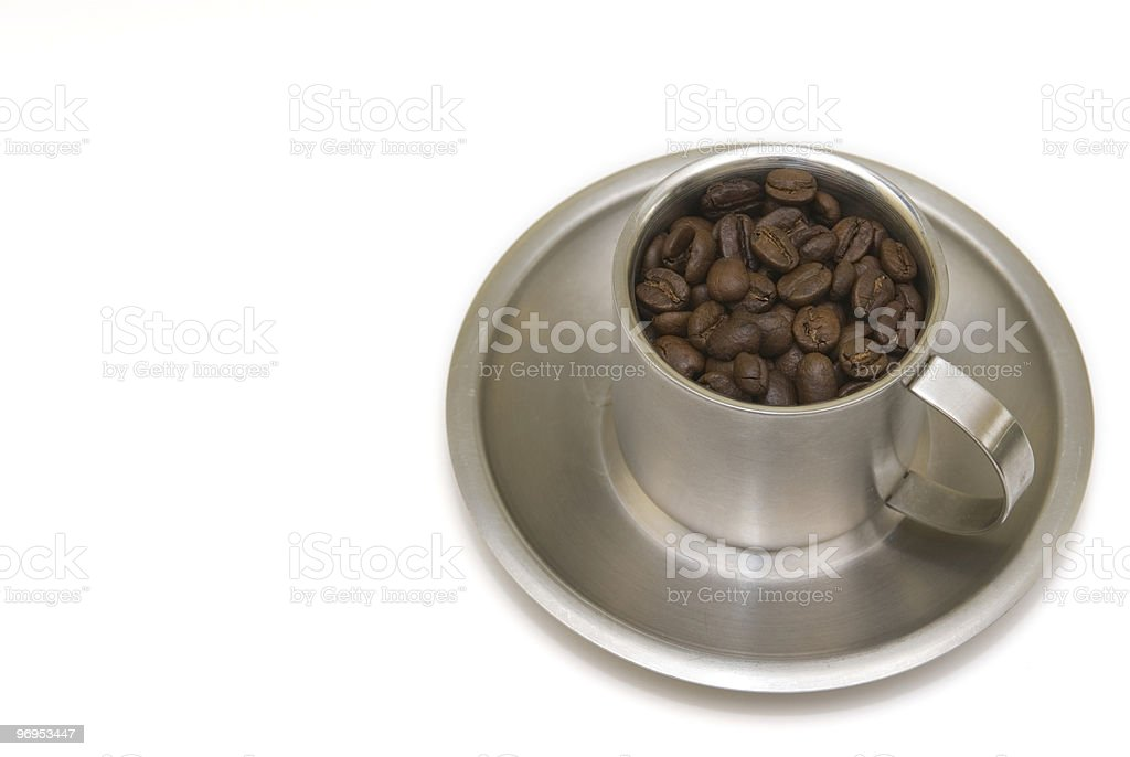 Cup on saucer filled with coffee beans. royalty-free stock photo