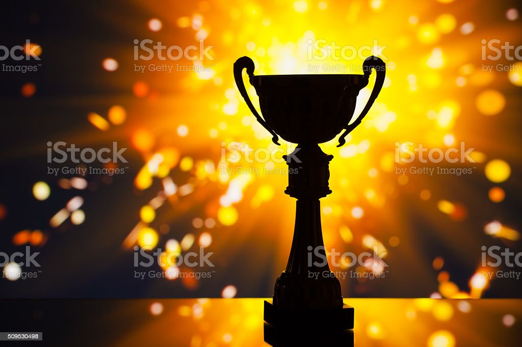 cup trophy silhouette against shiny sparks background stock photo