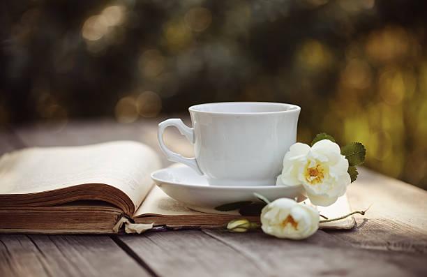 cup with a flowers of rose on an open book - rosen tee stock-fotos und bilder