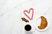 istock Cup with black coffee, croissant, caramel cane on a marble background. Concept bakery, pastries, french breakfast, christmas, morning, eve. Flat lay, top view 1280493238
