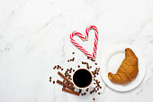 istock Cup with black coffee, croissant, caramel cane on a marble background. Concept bakery, pastries, french breakfast, christmas, morning, eve. Flat lay, top view 1280494085