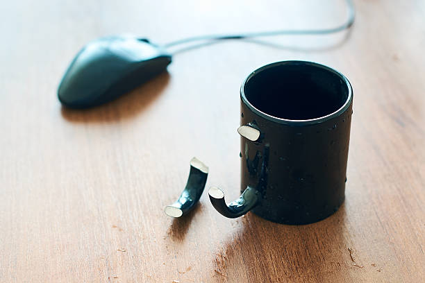 Cup with broken handle on the office table stock photo