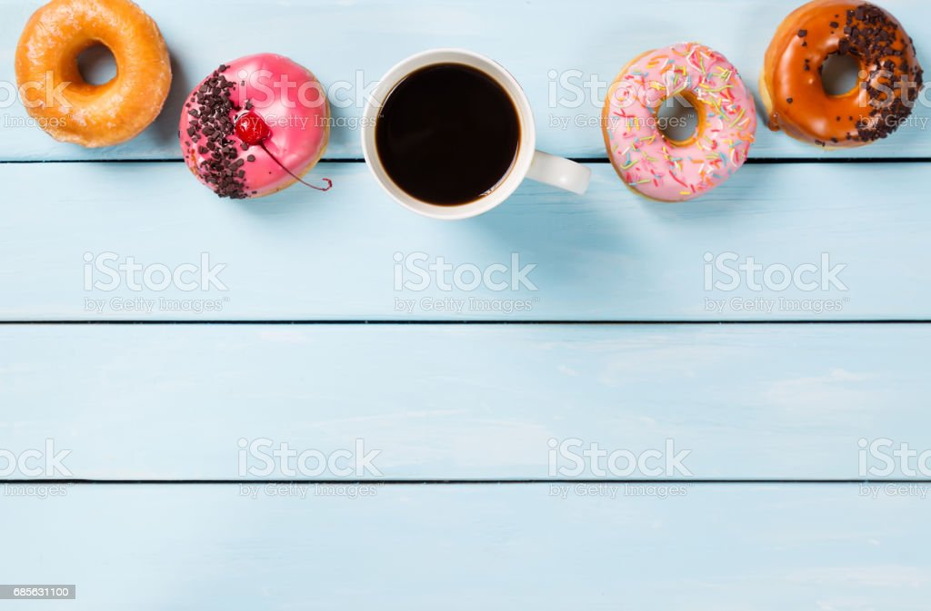 Cup with coffee and donuts on blue wooden table. Top view and free space for your text foto de stock royalty-free