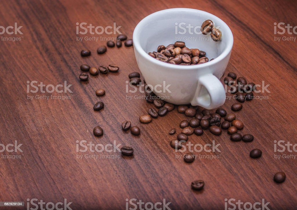 Cup with coffee beans on a brown tree royalty-free stock photo