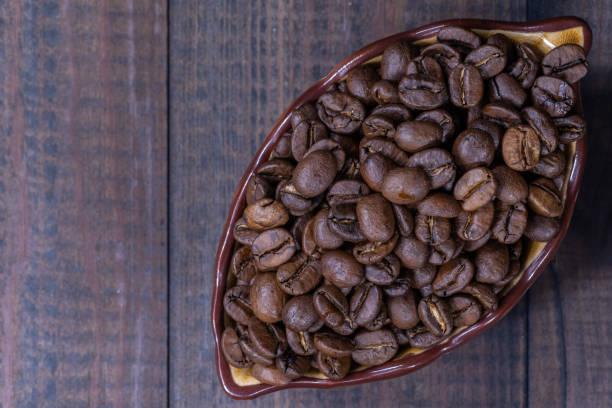 Cup mit Kaffeebohnen auf Holzplatte – Foto