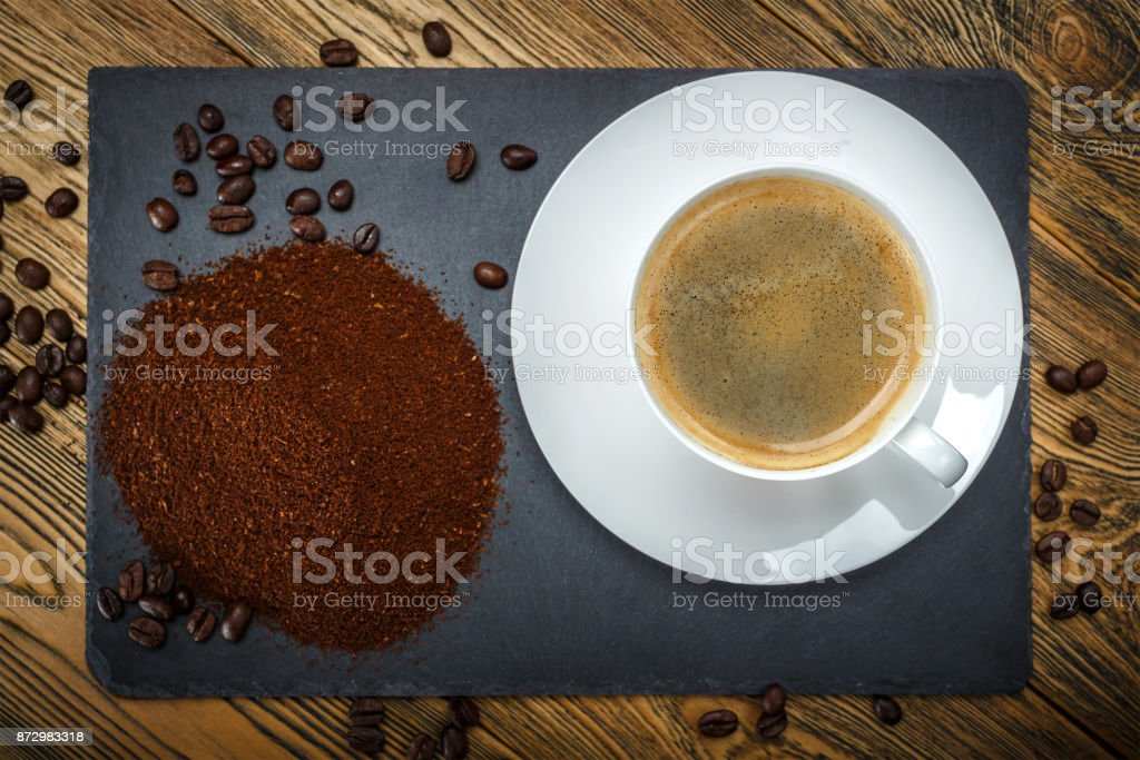 A Cup with coffee, ground coffee and coffee beans. The view from the...
